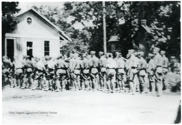 The Corps of Cadets are at rest near the C&O depot on Railroad Avenue during the 4th of July parade, 1919.  'Just before the begining of Alderson, W. Va.'