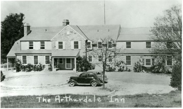 Front of the Arthurdale Inn with two cars parked outside.