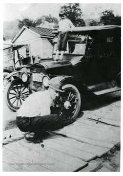 'Earl Hugh Moneypenny of Clarksburg, working on his car. Photo from 1927. Originial photo owned by a daughter, Pearl Moneypenny, of Clarksburg.'