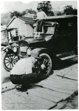 Earl Hugh Moneypenny crouched down near the front tire of his car. Small boy standing on car hood.  'Original photo owned by his daughter, Pearl Moneypenny of Clarksburg.'