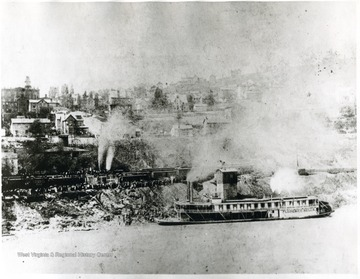 The Florence Belle pulling up to the edge of the river next to a train. 'At foot of Quincy St., showing Capt. Walker's House and Cal Arnett's home, one of the first modern homes in the city.'
