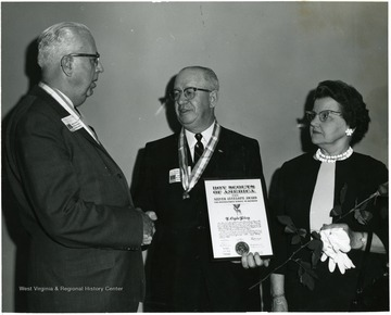 L. Clyde Riley shaking hands with a man upon receiving the Boy Scouts of America Silver Antelope Award.