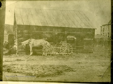 A horse drawn wagon is in front of an unidentified log building in Fairmont, West Virginia.