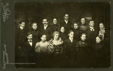 Graduating Class of 1898, Fairmont State Normal School in Fairmont, West Virginia. Graduating members are Sam Butcher, Jessie Hickman, Opha Lewis, Hallie Martin, W. J. LaFollette, Hallie Swan, Laura F. Lewis, Okay J. Woodford, Katharine B. Curry, Arthur P. Jones, Clara Reischuimer, Dora V. Wise, Ora L. Potter, Levi B. Harr, Helen M. Fleming, and Elizabeth Bartholow.
