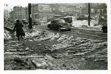 A person is walking on the sidewalk of Jackson and Monroe Street in Fairmont, West Virginia during the big snow storm of 1950.