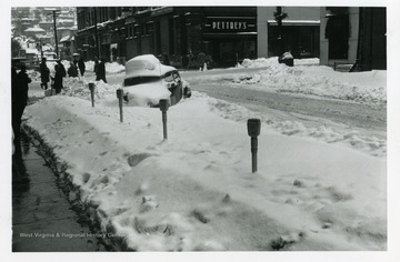 People are walking on Monroe and Adams Streets in Fairmont, West Virginia during the big snow storm of 1950.