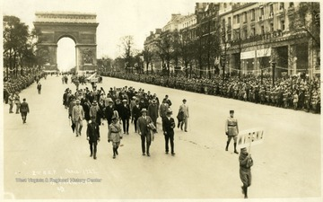 2nd A. E. F. in Paris, 1927.  From undated Charleston Daily News clipping, 'This photograph of the Legion parade taken in the French Capitol during the convention last summer has just been received by Boyd B. Stutler, secretary of the delegation.   It shows the West Virginia delegation just after it had passed under the Arch de Triomphe where each man placed a flower on the grave of the Unknown soldier.  Colonel Lewis Johnson, of Clarksburg, chairman of the delegation is marching in the head with his overcoat on his arm.  To his left is Mr. Stutler, and immediately behind Mr. Stutler, wearing the big hat is C. M. (Casey) Jon [sic] In the foreground is William Morris Stutler, young son of Mr. Stutler, carrying the state's banner.  Among the 21 Charlestonians in the group are Harry Kessell, Ben Bioarsky, John Crockett, and Mrs. Cora B. Haynes.'