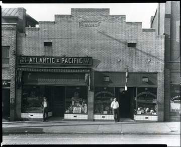 Outside view of The Great Atlantic and Pacific Tea Co. Grocery Store in Grafton, W. Va.  Two men standing in front of the entrances.