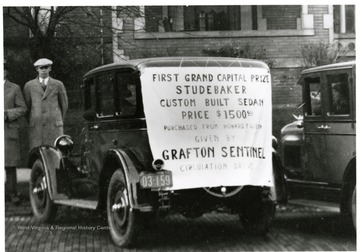 Man stands behind a custom built Studebaker, the First Grand Capital Prize Given by the Grafton Sentinel during a circulation drive.