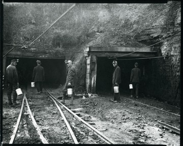 Five coal miners carrying lunch buckets enter shafts at an unidentified coal mine near Grafton, West Virginia.
