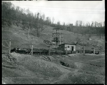 Two miners ride the locomotive leading a train of filled coal cars.