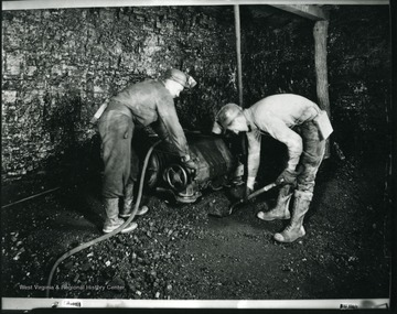 A miner is shoveling coal while another miner is operating a machine at an unidentified coal mine near Grafton, West Virginia.