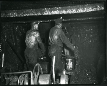 Two miners are working with a machine in an unidentified coal mine near Grafton, West Virginia.