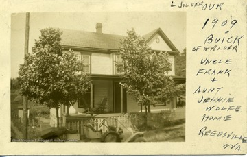 "Postcard of a house ""Uncle Frank [and] Aunt Jenni Wolfe's Home"" in Reedsville, W. Va. with a 1909 Buick belonging to W. R. Loar parked in front."