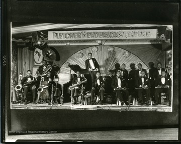 Fletcher Henderson Stompers pose with their instruments on stage.