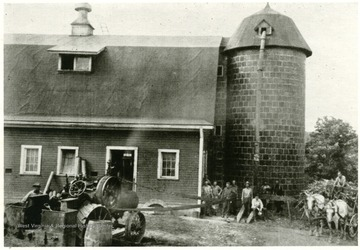 A belt is hooked up to a tractor. Group of men stand next to a silo attached to the barn.