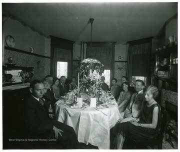 People seated around an elaborate dinner table.