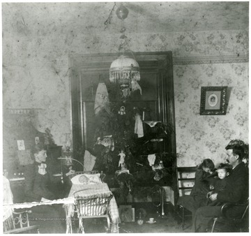 Christmas in the Robinson Home on West Main Street in Grafton, W. Va.  Fannie E. and W.R. Loar, Madue, Grace, and Leslie gathered around the Christmas tree.
