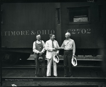 Three Baltimore and Ohio workers standing in front of a B and O train engine, Grafton, W. Va.