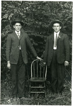 Two young men standing by a chair.  'Paul A from one Fred Burky.'