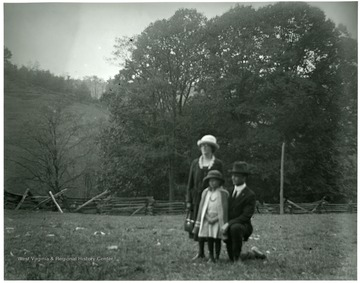 Olga Aegerter Holtkamp, Benjamin Holtkamp, and a young girl standing in fenced in field area in Helvetia, W. Va.