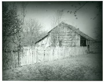 Gottfried Aegerter's first home in West Virginia.  A wooden house stands behind a wooden picket fence, and is surrounded by lots of trees.