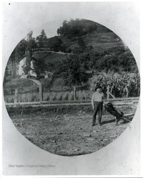 A gentleman is playing with his dog in a field in front of a church and a corn field.