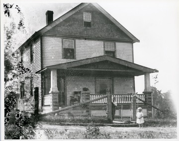 Two young children, an older boy and a younger girl, are standing by a gate near a porch of a two-story wooden house, location unknown.