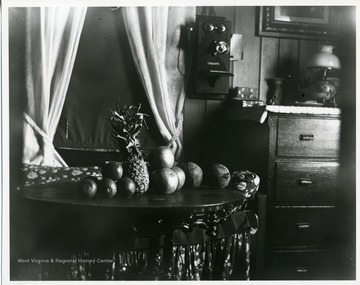 A pineapple and other round fruit are sitting on a table near a dresser and a phone in a home in Helvetia, West Virginia.