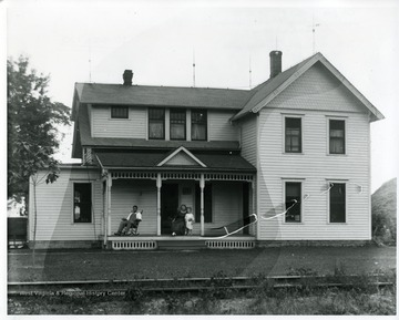 A man is sitting in a rocking chair while a lady is holding a child on the front porch, possibly West Virginia.