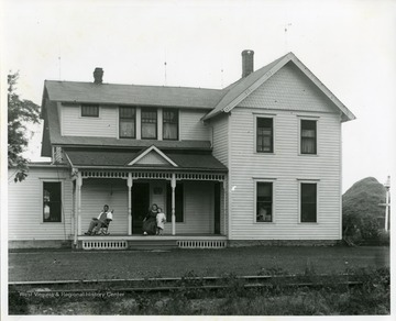 A man is sitting in a rocking chair while a lady is holding a young child on the front porch of a two-story house thought to be in West Virginia.