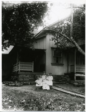 Four young children and a lady are standing in front of a porch of a house in Helvetia, West Virginia.