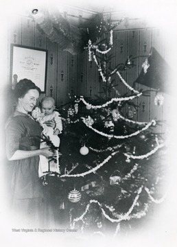 Olga Aegerter Holtkamp and baby place decorations on the Christmas tree.