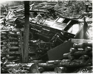 Three men stand amongst the wreckage of a train and piles of logs.