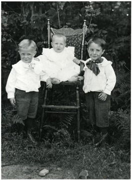Two boys stand next to a baby sitting in a chair.