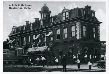 Postcard of a train engine and people outside of the C and O Depot in Huntington, West Virginia. See original for correspondence. (From postcard collection legacy system.)