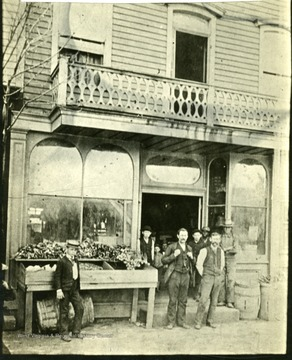 Men stand outside storefront. 'West side of 10th St. between 6th and 7th Avenues.'