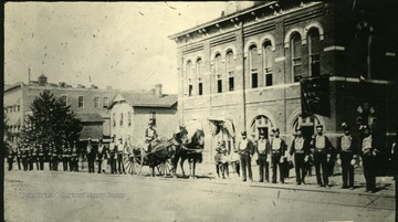 'Fire Department on parade, in front of old city hall, 9th St. between 4th and 5th Ave., where Deardorf Sisler store was located.'