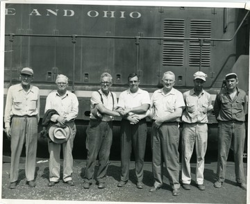 Seven Baltimore and Ohio Train Workers stand in front of a railroad car.