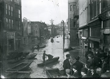 People riding in boats on flooded Market Street under a welcome sign, Parkersburg, W. Va.