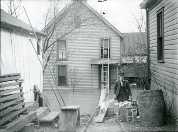 Man walking away from a flooded house.  Entrance to the house gained by a ladder up on the porch, Parkersburg, W. Va.