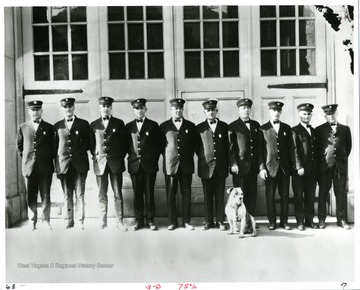 "Members of the Morgantown Fire Department, from left to right: ""Chief John Hare, John Rich, Mearle Devaughn, Homer Zearley, William Sherman, Rolla Dutton, Plummer Pride, Harry Feck, Dorsey Stalnaker and Friend Barrett. The dog is ""Doc,"" the mascot.""Photo appeared in the Morgantown Post on February 23, 1927."