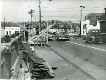 Cars pass as workers repair the University Avenue bridge.