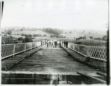Group of men standing near the middle of the bridge. Two are fighting.  Some men on the walkways of the bridge. Edge of bridge can be seen. In the distance you can see hills and the pathway.