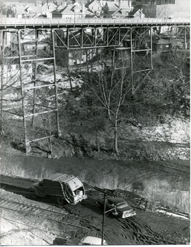 Deckers Creek and Elk Street. Morgantown and Kingwood railroad tracks. Two vehicles can be seen off of the railroad tracks. Creek at bottom near vehicles.  Neighborhood on far side of the bridge.