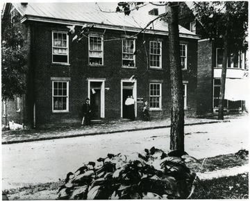 'Dr. Fielding Yost and wife Malanda Ann Yost lived in this house in Morgantown, W. Va.  This is on Main St.  They put three sons through college to be Dr.'s.  Copied from back of picture owned by Lewis Stemple, loaned to Dr. Core for Copying - written Mar. 1978; Is this on the west side of High Street or corner of Wall Street?  Marion Tapp thinks it is the Franks Home, S. W. corner of Fayette St. and University Ave.  She lived near there as a child.  A double home is on the site of the Morgantown plat of 1921.'