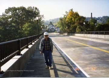 Construction worker walking across completed South Park bridge.