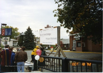 A group of people can be seen near the end of the South Park bridge surrounding a table. Behind the group of people is a display sign for the Project Mohawk.