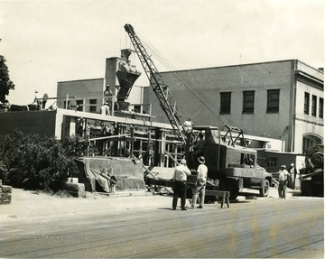 Construction on public library. Workers can be seen on the road on and the building.