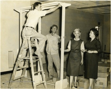 Librarians look on as two men construct shelving unit.